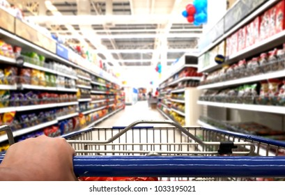 Hand pushing trolley in supermarket