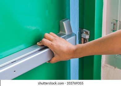 Hand is pushing/opening the emergency fire exit door