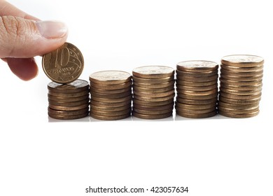 Hand put 10 cents coin to pile of brazilian coins (money) on white background