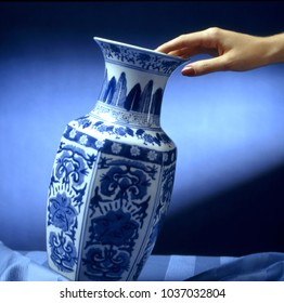hand put a china style decorated ceramic vase on a table
