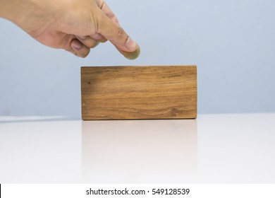 Hand put coin in the wood box for saving money