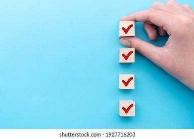 Hand, die den hölzernen Würfel mit rotem Häkchen für die Checkliste oder die Liste ablegt