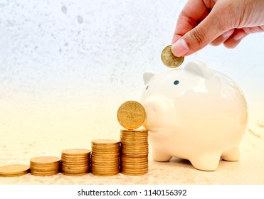 Hand put gold coin into piggy bank with rolls ladder of money in orange white color tone
