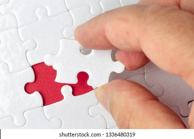 Hand put the last piece of jigsaw puzzle to complete the mission