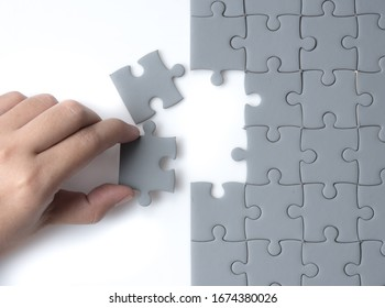 Hand put the last piece of jigsaw puzzle, success, teamwork and finishing or ending