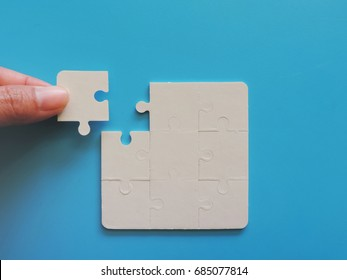 Hand put the last piece of jigsaw puzzle to complete the mission,Concept of business.