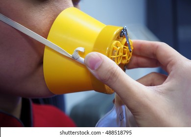 Hand put on the cabin oxygen mask over the  mouth and nose.