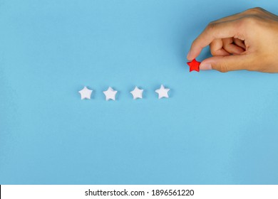 Hand put paper red star in whie row on blue background. Giving review, Sale rating and customer satisfaction concept.
