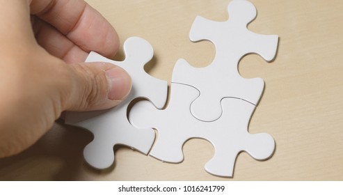 Hand put the piece of jigsaw puzzle