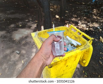 Hand put the trash (drinking water plastic cup) in the trash bin after used. one activity one pollution concept.