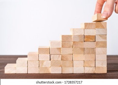 Hand put wooden blocks in shape of staircase. Building success foundation concept.