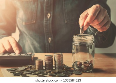 hand puting coins into jug glass for saving money finance and accounting concept