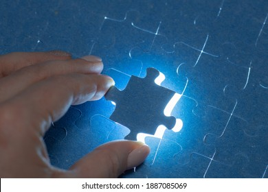 the hand puts the last piece of the puzzle, the solution of the puzzle, the end of a large project, the completion of work,