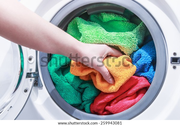 hand and puts the laundry into the washing machine. focus on a colored towel