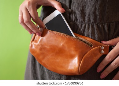 Hand puts phone to waist bag made from natural leather close-up view on the unrecognizable woman on the green background. Concept of city accessoires and travel