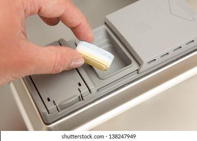 Hand puts tab into dishwasher