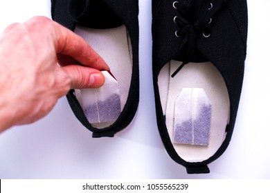 hand puts the tea bag in shoes. concept of removing unpleasant odors