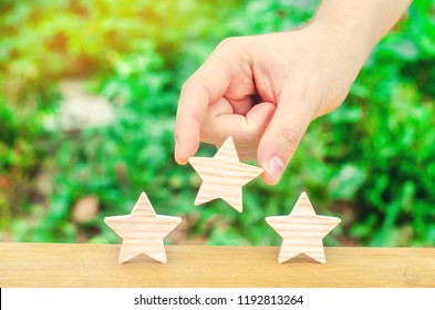 The hand puts the third star on a green background. Quality assessment and popularity. Overview of the restaurant or hotel. Awarding the highest score, recognition and praise. Success and luck.