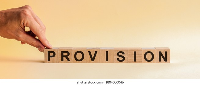 The hand puts a wooden cube with the letter P from the word PROVISION. The word is written on wooden cubes standing on the yellow surface of the table. Concept.