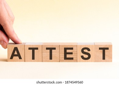 The hand puts a wooden cube with the letter A from the word Attest. The word is written on wooden cubes standing on the yellow surface of the table.