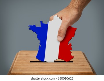 Hand putting a ballot with shape of the map of France in box.