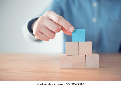 Hand putting blank blue wood cube block on top pyramid, for create icon symbol to success concept.
