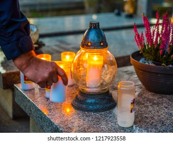Hand putting candles and flowers on graves on All Saints Day in Poland