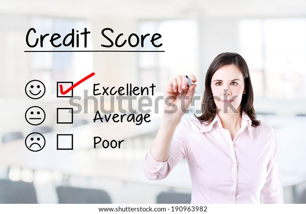 Hand putting check mark with red marker on excellent credit score evaluation form. Office background.