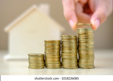 hand putting coin with house model background, gold coins stack on wooden table in the morning sunlight. business, investment, retirement, finance and Money Saving for the future concepts