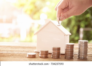 Hand putting coin in house model of coin for saving money for buying house