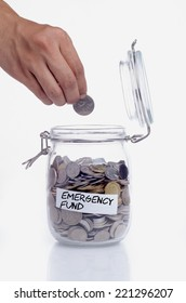Hand putting a coin into glass jars with 'emergency fund' text: Saving for emergency fund