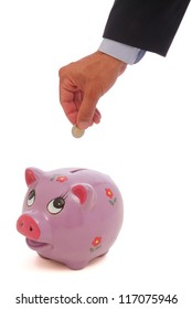 A hand putting a coin into a piggy bank isolated on white background