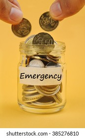 """Hand Putting Coin In Jar with Word """"EMERGENCY"""", Selective Focus"""