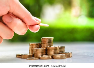 Hand putting coin to stack of coins. Saving money concept.