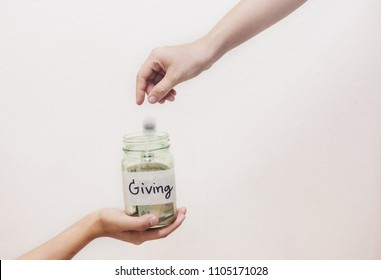 Hand putting Coins in glass jar with Giving word written text label for giving and donation concept