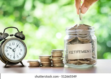 Hand putting Coins in glass jar for with retro alarm clock  for time to money saving for retirement concept