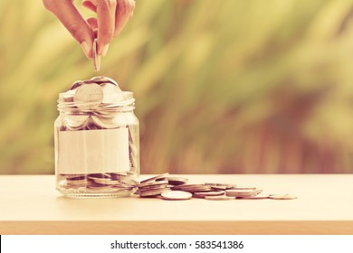 Hand putting Coins in glass jar with blank empty label for giving and donation money concept , can use for financial background and add any text on label by yourself