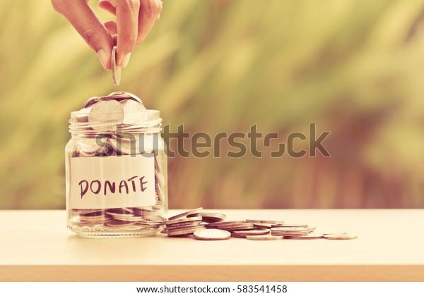 Hand-Pin-Coins in Glasjar mit DONATE-Textbeschriftung für Spende- und Spendenkonzept