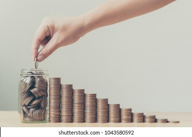 Hand putting coins in jar with money stack step growing growth, Saving money or investment financial plan with efficiency and quality to increase sustainable growth and stability in the future