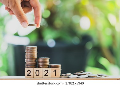 A hand putting the coins on the wooden table like a growing graph. with text 2021, On green blurry bokeh background. And copy space. Saving money and finance concept.