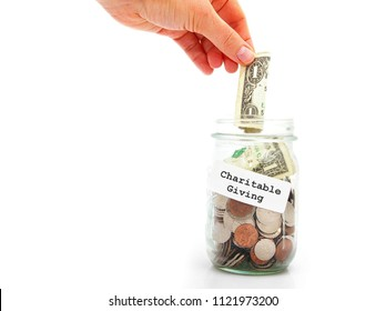hand putting a dollar into Charitable Giving jar, isolated on white