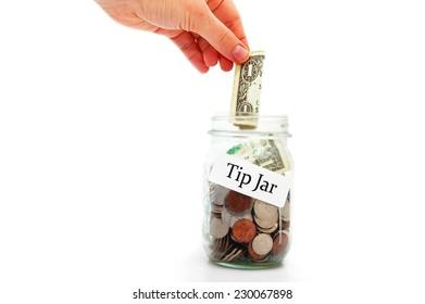 hand putting a dollar into a tip jar