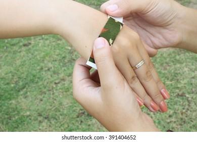 hand putting elastic plaster on  hand injury