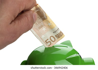 Hand putting Euro banknote on a piggy bank isolated on white.