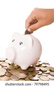 Boy´s hand putting a euro coin in a piggy bank