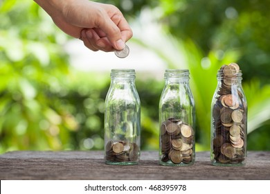 Hand putting gold coins in egg cracked into bottle on natural background,Business investment growth concept