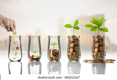 Hand putting Gold coins and seed in clear bottle on cityscape photo blurred cityscape background,Business investment growth concept