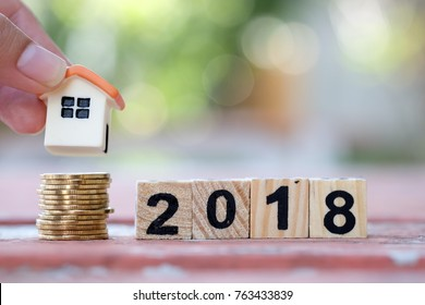 Hand putting house on stack of coins. Concept of Saving money for buy property in year 2018