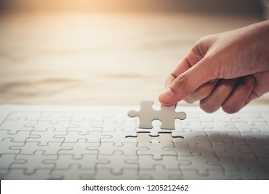 Hand putting last piece jigsaw puzzle to complete mission., Closeup of woman hands fulfill the last piece of jigsaw puzzle to complete.,Business solutions, success mission concept.