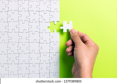 Hand putting the last piece of white jigsaw puzzle on green background and place for your content